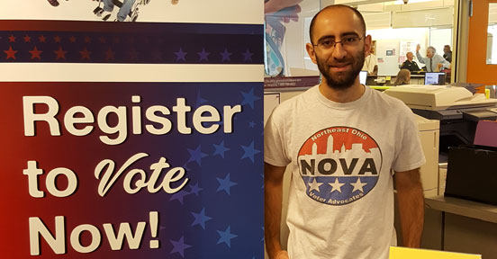 Man next to Register to Vote Now! sign.